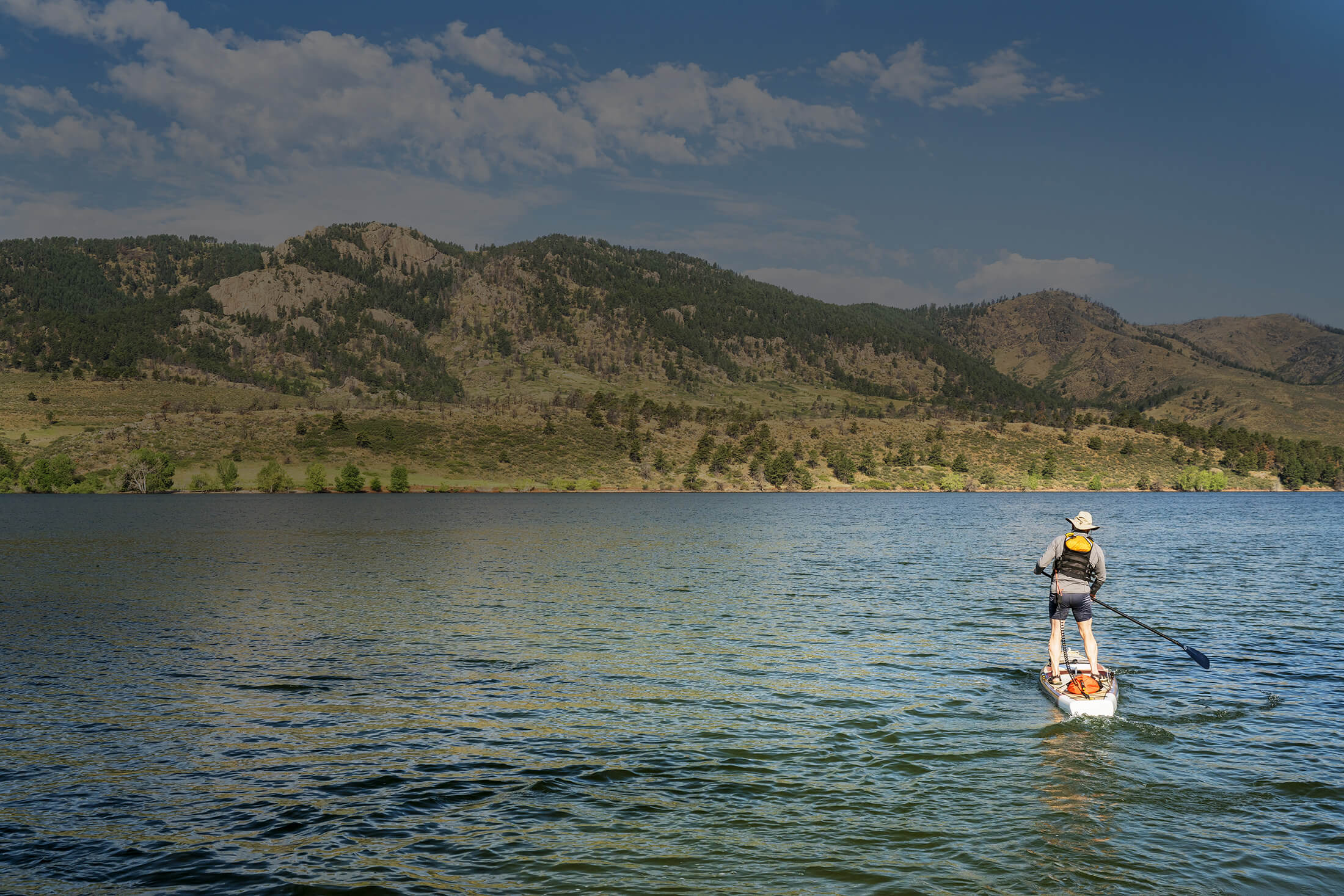 Pure Drip IV Health & Wellness About Us Man Paddleboarding Horsetooth Reservoir